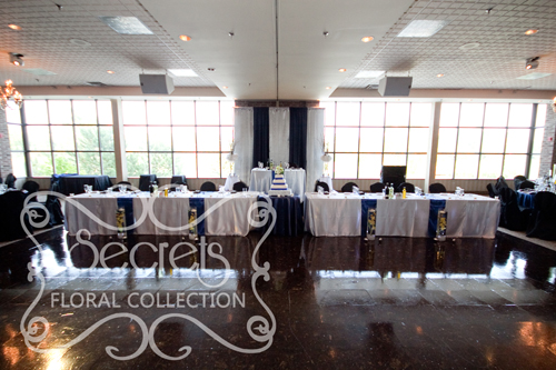 A Navy Blue and Silver Backdrop and Tables