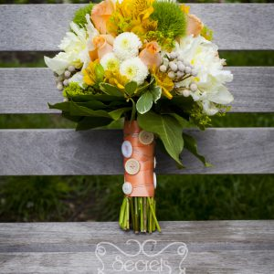Fresh white peonies, peach roses, yellow alstroemeria, green trick dianthus, lady's mantle, white button mums (ice caps), and silver brunia berries bridal bouquet, with a peach ribbon and white buttons wrap (front-view) - Toronto Wedding Flowers by Secrets Floral Collection