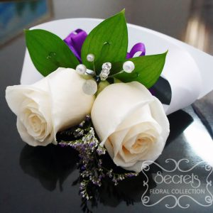 Fresh double-bloom cream roses and purple limonium wristlet corsage, with purple bow and jewel embellishments (top-view) - Toronto Wedding Flowers Created by Secrets Floral Collection