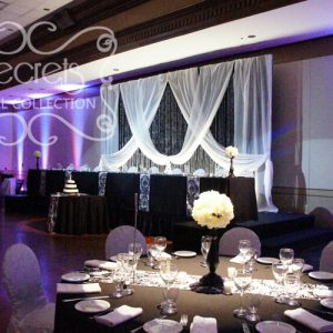 Black, White, and Bling Backdrop. Room is Decorated with Blue and Pink Uplights.