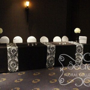 Black Receiving Table with Damask Runners and White Brocade Chair Covers
