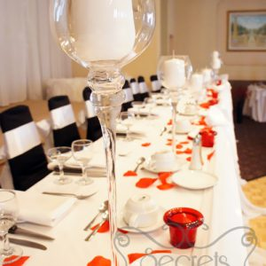 Set-up of Head Table, with Red Petals, Red Candles Holders, and Tall Stemmed Glass Candle Holders
