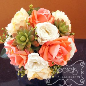 Bridal bouquet with coral pink roses, white ranunculus, succulents, and eucalyptus bridal
