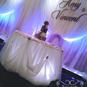 Cake Table with Cream Voile Cinderella Skirting and White Spotlights