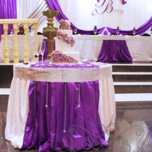 Cake table decorated with white crinkled linen and purple satin stripe. Table is crystallized with the Bling! Bling! edge and suspending crystal strands