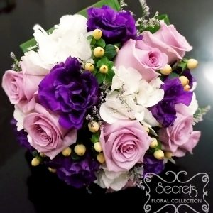 Fresh lavender roses, purple lisianthus, white hydrangea, ivory hypericum berries and misty blue limonium bridal bouquet, with ivory satin wrap with pearl and diamond brooch
