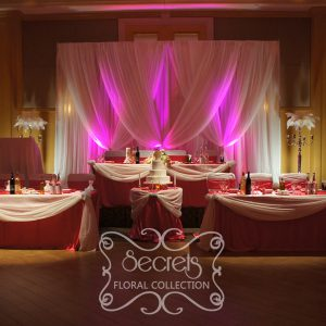 Setup of the cream voile backdrop with fuchsia LED uplights, and split head table with fuchsia satin and cream voile swags
