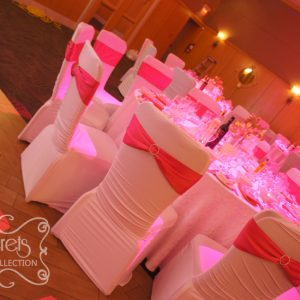 Chairs are dressed in white spandex (Giselle) chair covers, with fuchsia chair band and Swarovski crystal buckle