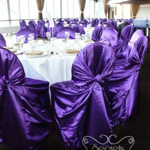 Guest chairs are dressed with royal purple satin chair covers