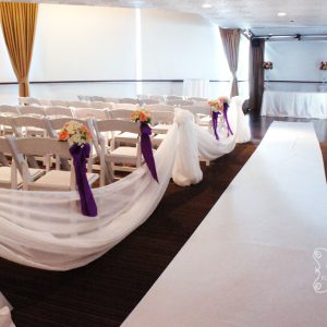Aisle is lined with premium satin fabric for a extravagant look. Sides of the aisle are decorated with cream voile swags and flowers.