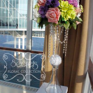 Each arrangement is made with purple anemone, salmon pink roses, (green, lavender, and white) hydrangea, and (white and green) lilac, on reversible vase with crystal strands