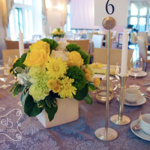 Low-profile centrepiece with fresh yellow roses, yellow cushion mums, green trick dianthus, light green carnations, succulents, cream hydrangea, yellow button mums, and dusty miller, in white cube pot (side-angle)