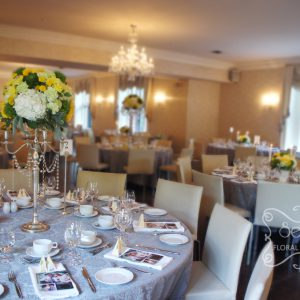 Guest tables are dressed in silver damask tablecloths. Very modern against the white chairs