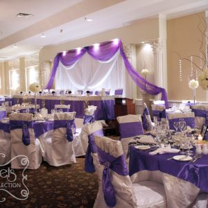 Guest tables are dressed with purple overlay and damask runner. Chairs are tied with purple sashes. - Toronto Wedding Decor Created by Secrets Floral Collection