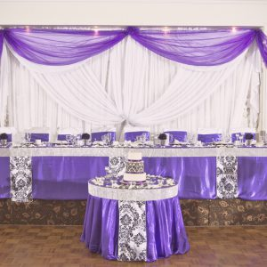 A purple and damask backdrop and tables. Head and cake tables are lined with crystal mesh around the edge to add a lot of sparkles - Toronto Wedding Decor Created by Secrets Floral Collection