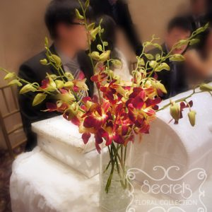 Two-tone fuchsia and peach dendrobium orchids arrangement, on receiving table - Toronto Wedding Decor Created by Secrets Floral Collection