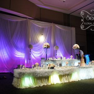 Ivory backdrop with a touch of light pink LED lights. Backdrop is crystallized with crystal panels and with spiral chandelier - Toronto Wedding Decor Created by Secrets Floral Collection
