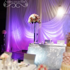 Tall head table floral arrangement with white, cream, and light pink flowers (roses, garden roses, peonies, hydrangea), on a crystal stand - Toronto Wedding Decor Created by Secrets Floral Collection