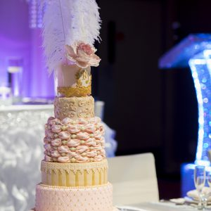 Beautiful and luxurious pink and gold wedding cake, with white ostrich feathers cake topper. Photo by Andes Lo Photography - Toronto Wedding Decor Created by Secrets Floral Collection