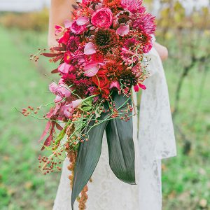 A large, oversized, waterfall (cascade) bouquet, filled with fresh fuchsia garden roses, read roses, pink calla lilies, burgundy cremons, hot pink spider mums, protea, gloriosa, tinted red seeded eucalyptus, red rberries (rose hips), and hanging amaranthus - Toronto Wedding Flowers by Secrets Floral Collection