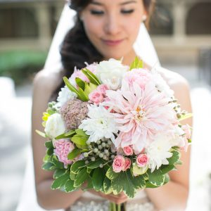 A romantic bridal bouquet, with blush dahlia (cafe au lait), cream garden roses, white cymbidium orchid, light pink spray roses, sedum, olive green leucadendron, and berzillia berries - Toronto Wedding Flowers by Secrets Floral Collection
