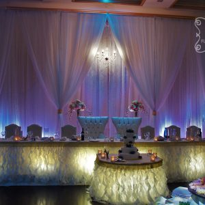 Pink crystallized backdrop with crystal chandelier.. Head and cake table with ruffles and accent with gold bling- Toronto Wedding Decor Created by Secrets Floral Collection