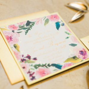 Detail shot of gold foliage and gold and floral themed wedding invitations. Cinderella themed style shoot located at the Victorian Convention centre, Missisauga.