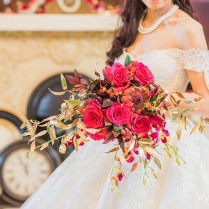 Flowy bridal bouquet with hot pink roses, red hypericum berries, red leucadendron, red protea, fuscia dendrobium orchids and gold foliage. Open shoulder lacey, Cinderella wedding dress. Flowers by Secrets Floral.