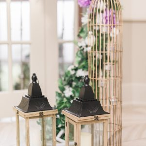 Rustic wood lantern and gold birdcage beside ceremony arch. Toronto wedding flowers and decor at Fontana Primavera by Secrets Floral.