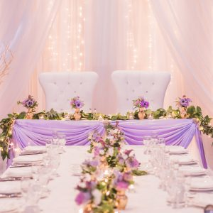 Wedding reception, with twinkle lights backdrop, and lavender head table. Dressed with purple floral and greenery garland. Toronto wedding flowers and decor at Fontana Primavera by Secrets Floral.