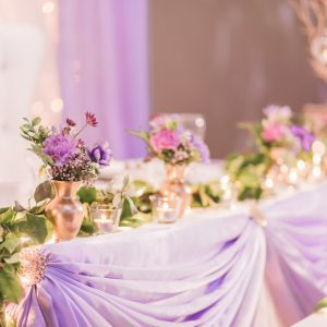 Wedding reception, with twinkle lights backdrop, and lavender head table. Purple flowers in gold bud vases. Toronto wedding flowers and decor at Fontana Primavera by Secrets Floral.