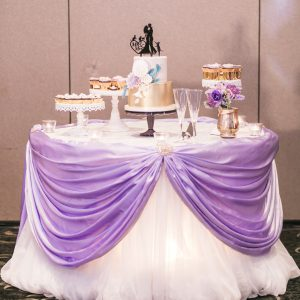 Wedding reception cake table. Dressed with lavender purple satin swag and cream chiffon table skirt. Toronto wedding flowers and decor at Fontana Primavera by Secrets Floral.