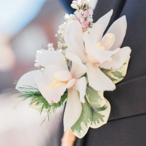 Groom boutonniere with white cymbidium orchids and pink heather flower. Toronto wedding flowers by Secrets Floral.